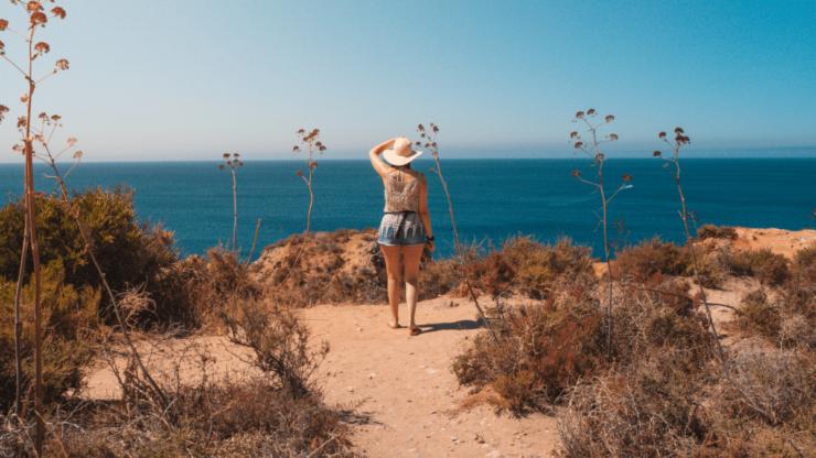 mulher de frente para a praia observando a paisagem